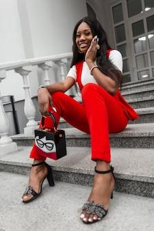 Muito positiva mulher moderna africana com um lindo sorriso no elegante terno vermelho em elegantes sandálias com bolsa elegante sente-se na escadaria de pedra na rua. positiva garota negra na moda vestido ao ar livre.