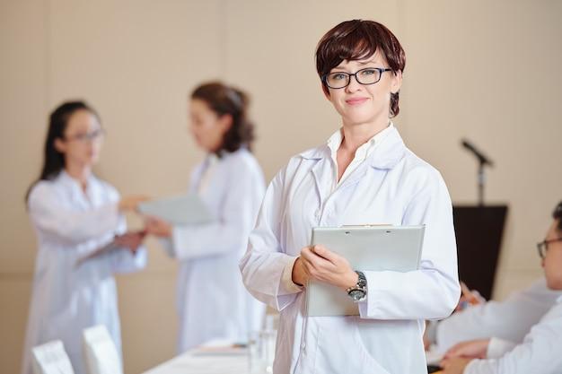 Muito positivo jovem médico em jaleco em pé com uma prancheta nas mãos, seus colegas falando ao fundo