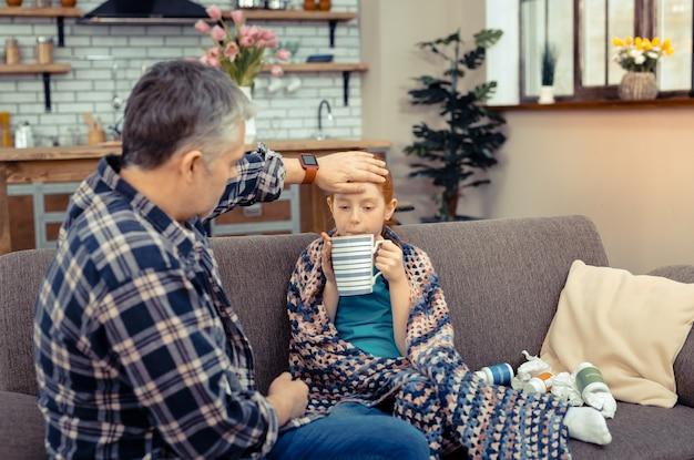 Muito saboroso. menina deprimida e infeliz segurando uma xícara enquanto toma um gole de chá