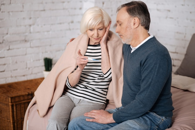 Muito. senhora idosa surpresa está olhando para o termômetro enquanto está sentada coberta com um cobertor perto do marido.