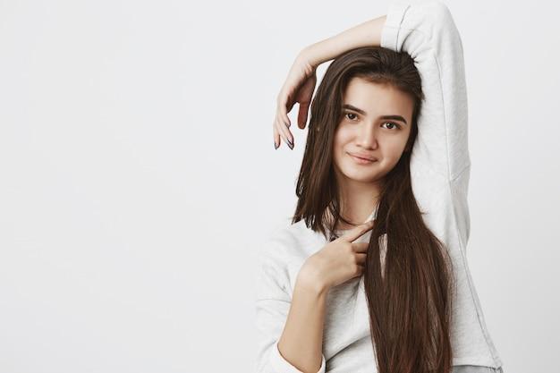 Muito sorridente com alegria mulher adolescente com cabelos longos escuros, posando dentro de casa, vestida casualmente.