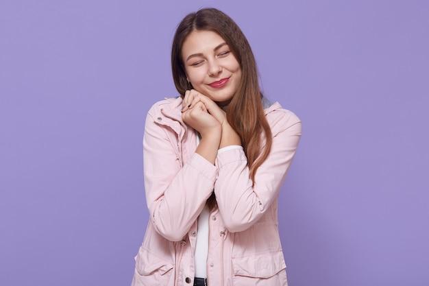 Muito sorridente encantadora jovem vestindo jaqueta rosa pálida, segurando os punhos perto de bochechas isoladas na parede lilás, mantendo os olhos fechados, parece fofa, mulher com cabelo longo e bonito.