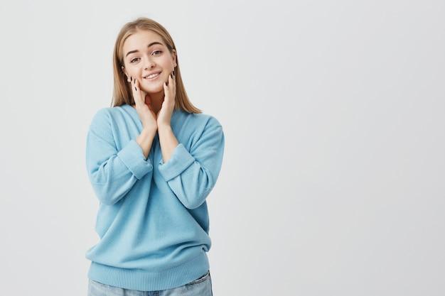 Muito sorridente jovem bonita cabelos louro olhando com olhos calmos, sendo o prazer de ouvir boas notícias. menina bonita que olha tocando suas bochechas, posando no estúdio.