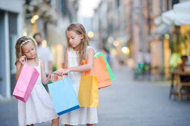Muito sorridente meninas com sacolas de compras