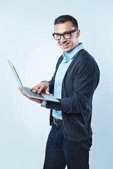 Muito trabalho a fazer. foto recortada de um cavalheiro animado ganhando um traje casual elegante com um sorriso largo enquanto olha para a câmera e navega na internet em um laptop.