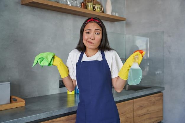 Muito trabalho, jovem faxineira olhando confusa para a câmera enquanto segura o spray de detergente