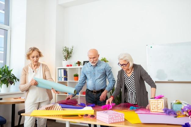 Muito trabalho. pessoas idosas com boa aparência em pé na frente da mesa enquanto olham para ela