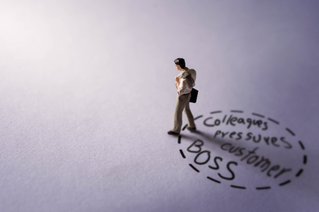 Muito um conceito de trabalho. presente pela figura miniatura do empresário tristeza