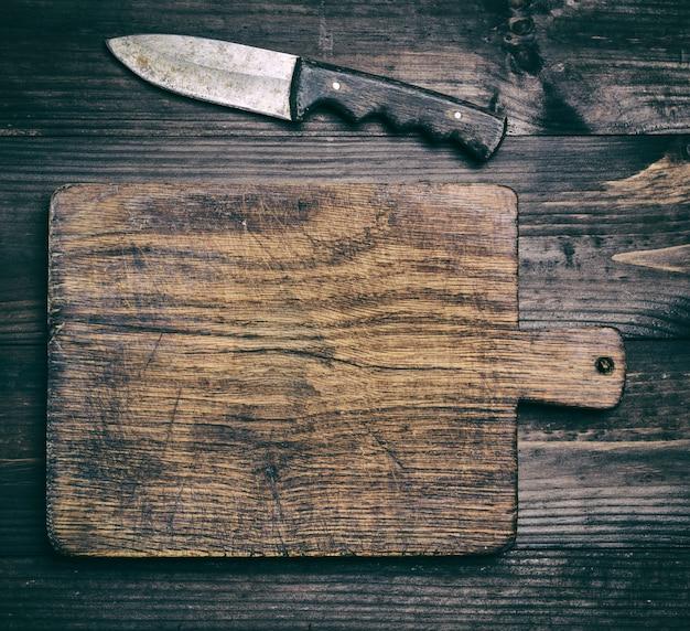 Muito velha tábua de madeira marrom e faca