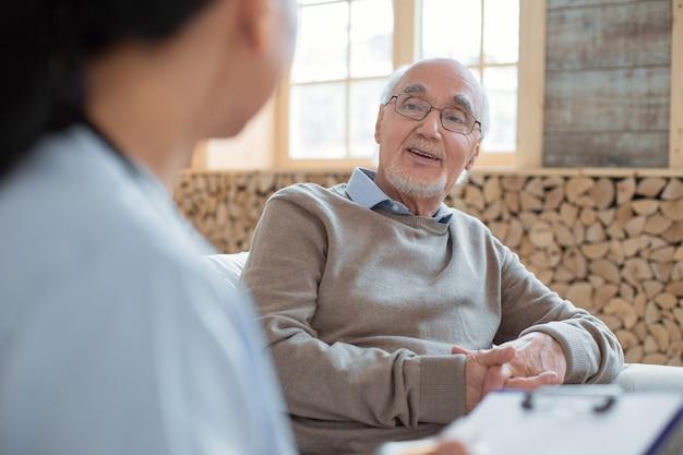 Muito velho. médico segurando a prancheta enquanto observa e ouve um homem feliz sênior positivo