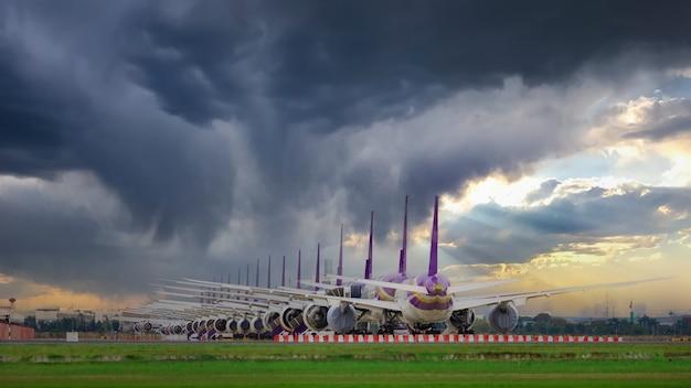 Muitos aviões estão em fila na pista aguardando a decolagem. esses aviões da força aérea fazem parte do serviço de parada da operação para transporte na situação covid-19. na tailândia