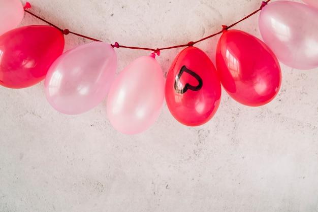 Muitos balões com coração pintado pendurado na torção