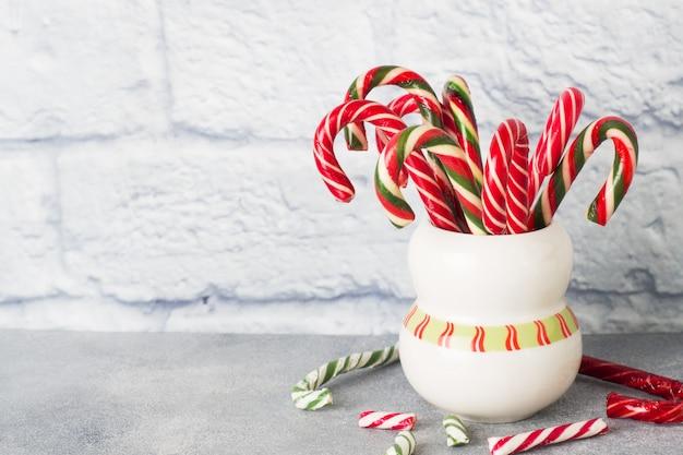 Muitos bastões de doces de natal em uma caneca em um fundo cinza com espaço de cópia. caramelo de natal festivo brilhante.