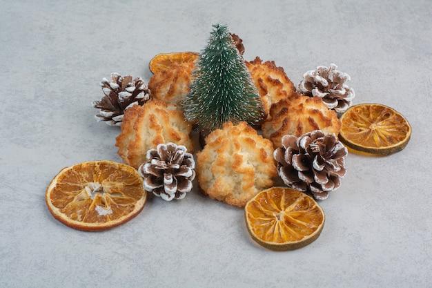 Muitos biscoitos frescos deliciosos com pequenas pinhas e laranjas secas.