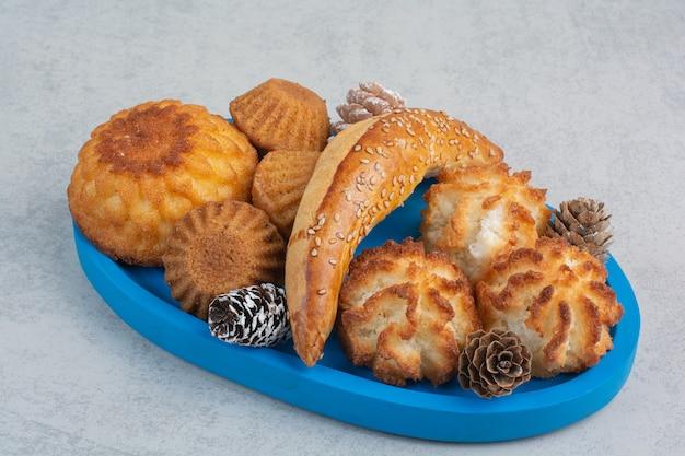 Muitos biscoitos frescos deliciosos com pequenas pinhas na placa azul.