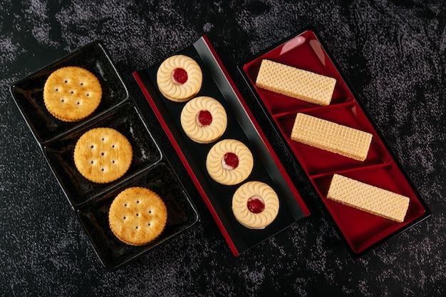 Muitos biscoitos são lindamente dispostos em um prato e depois colocados em uma mesa de madeira.