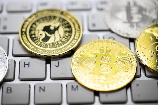Muitos bitcoins criptomoeda repousavam sobre o teclado branco. a moeda de ouro é a moeda importante para pagar tudo no futuro mundial global.