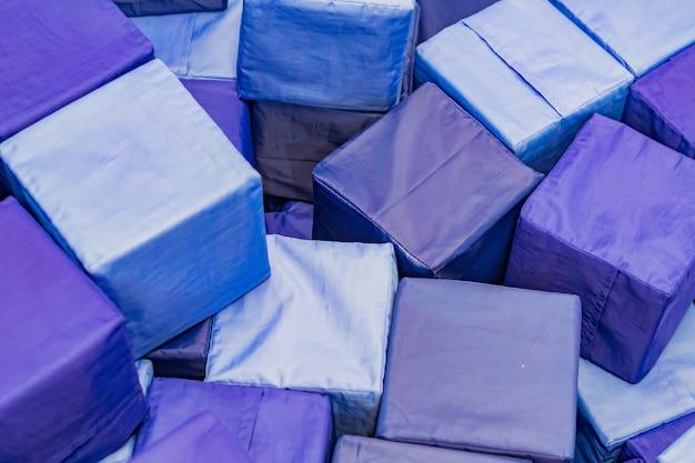 Muitos blocos azuis suaves na piscina seca de crianças no playground. brinquedos geométricos.