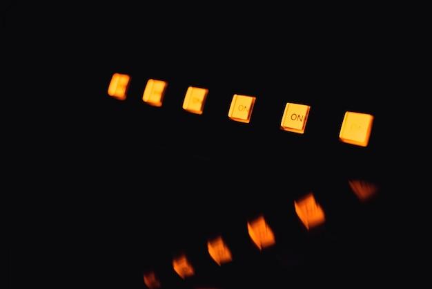 Muitos botões amarelos power on equipamento musical com reflexão