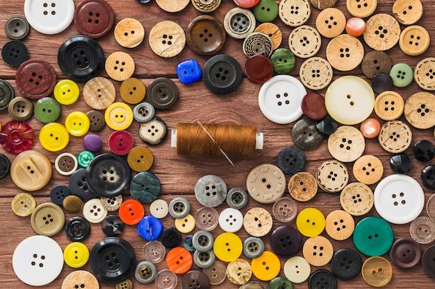 Muitos botões coloridos; linha marrom e agulha em fundo de madeira