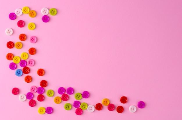 Muitos botões coloridos no fundo rosa. copyspace