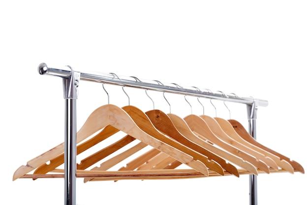 Muitos cabides vazios de madeira para roupas no rack em fundo branco. você não tem nada para vestir. venda