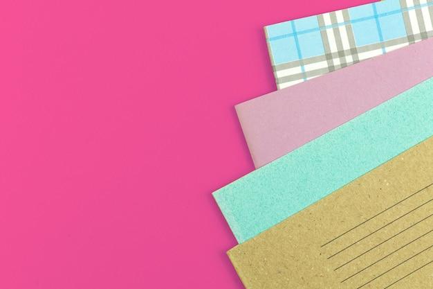 Muitos cadernos escolares na mesa rosa fora do fundo da área de trabalho, foto do plano de fundo do conceito da escola