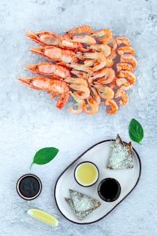 Muitos camarões reais crus frescos e camarões jumbo cozidos com molhos, torradas, limão, folhas de manjericão, cópia espaço, vista de cima, vertical, espaço para texto