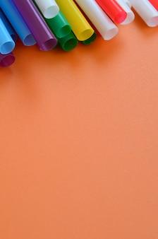 Muitos canudos coloridos para bebidas encontra-se em uma superfície de fundo laranja brilhante