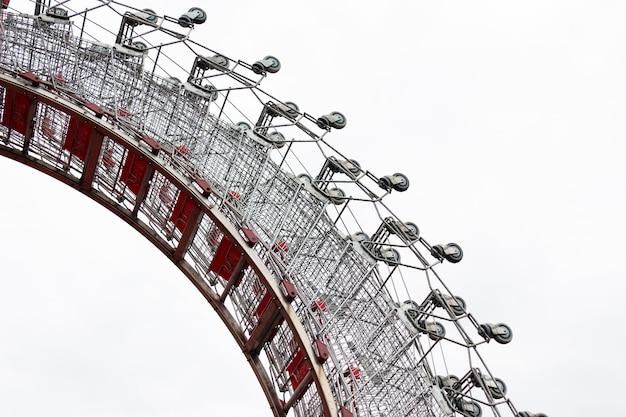 Muitos carrinhos de supermercado dobrados em um arco sobre fundo branco.