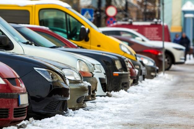 Muitos carros diferentes estacionados em uma cidade. carros a venda