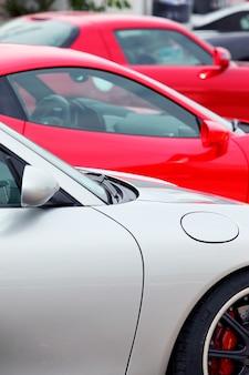 Muitos carros esportivos estacionados em uma fileira, visão vertical