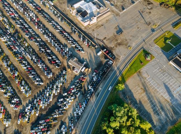 Muitos carros estacionados distribuídos em lote de leilão de carros usados um estacionamento.