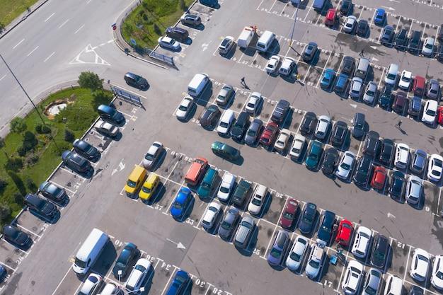 Muitos carros no estacionamento lotado em filas retas, do ponto de vista de pássaros