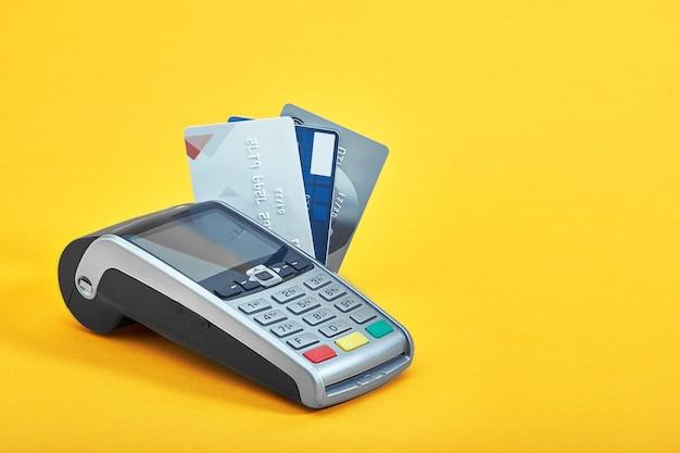 Muitos cartões de crédito diferentes e terminal de pagamento em fundo amarelo, closeup.