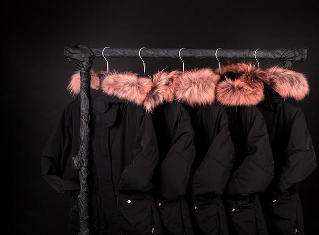 Muitos casacos de inverno pretos, jaqueta com pelo no capuz pendurada no cabideiro em fundo preto, sexta-feira preta