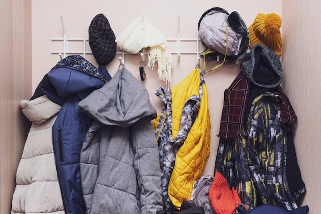 Muitos casacos e bonés de inverno, chapéus pendurados em uma bagunça em ganchos em um corredor, organizando roupas quentes.