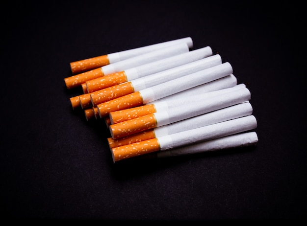 Muitos cigarros fecham em um fundo preto isolado