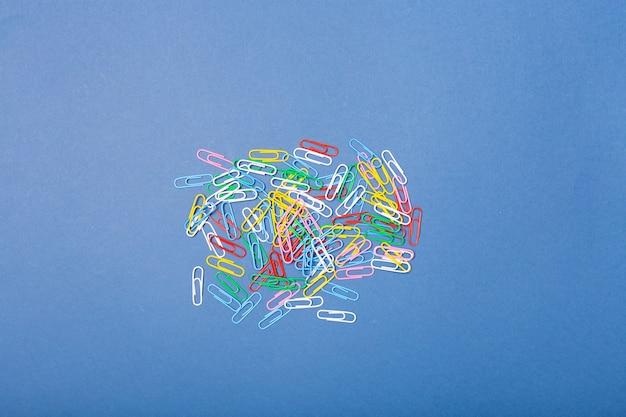 Muitos clipes de papel brilhantes coloridos sobre fundo azul. copie o espaço livre.