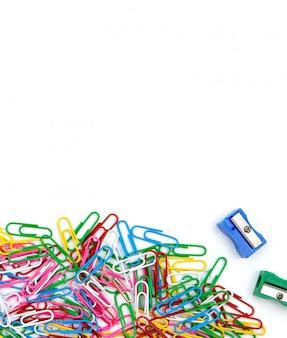 Muitos clipes de papel e sharpeners coloridos em um fundo branco. vista superior e espaço de cópia.