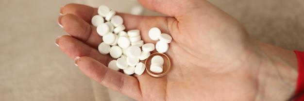 Muitos comprimidos brancos e um anel de casamento na mão da mulher.