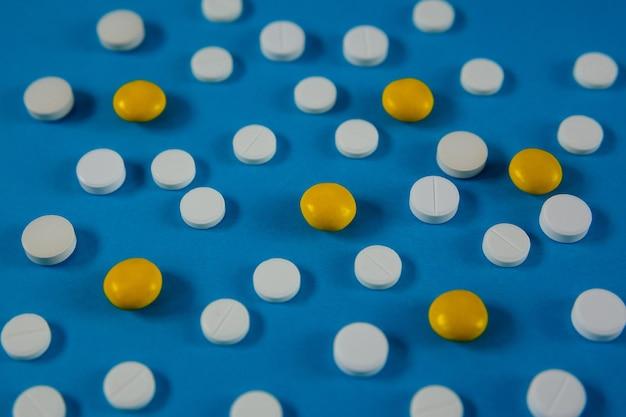 Muitos comprimidos brancos e vermelhos em um fundo azul