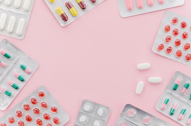 Muitos comprimidos coloridos blister no pano de fundo rosa com espaço de cópia para escrever o texto