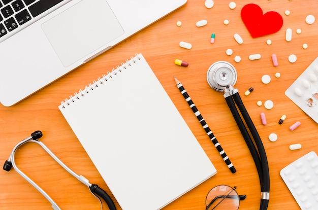 Muitos comprimidos coloridos com coração vermelho; estetoscópio; lápis; óculos e laptop na mesa de madeira