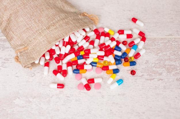 Muitos comprimidos coloridos diferentes no fundo da mesa