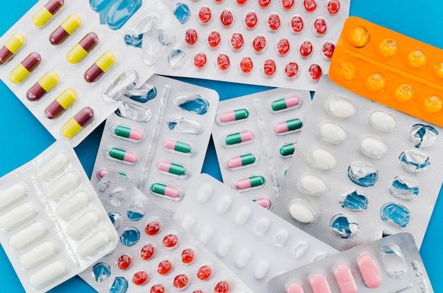 Muitos comprimidos coloridos em fundo azul