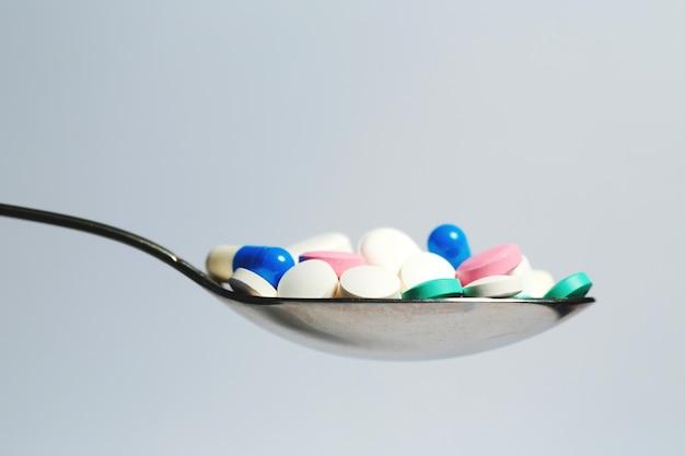 Muitos comprimidos coloridos em uma colher. foto simbólica para tablets dependência e abuso de drogas.