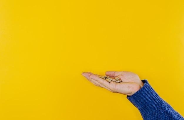 Muitos comprimidos comprimidos na mão de um homem em um fundo amarelo brilhante