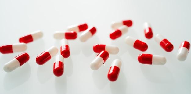 Muitos comprimidos de cápsulas vermelhas e brancas