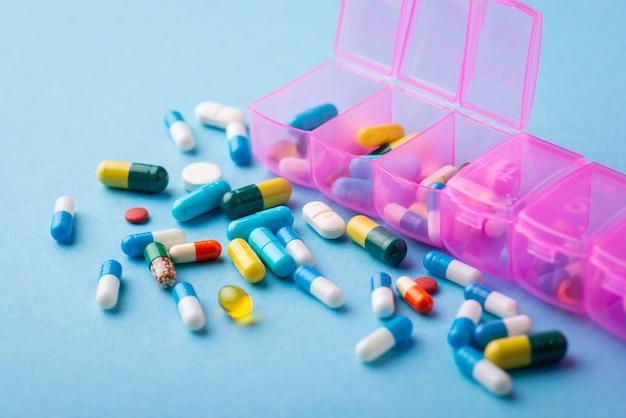 Muitos comprimidos diferentes em fundo azul perto da caixa organizadora rosa